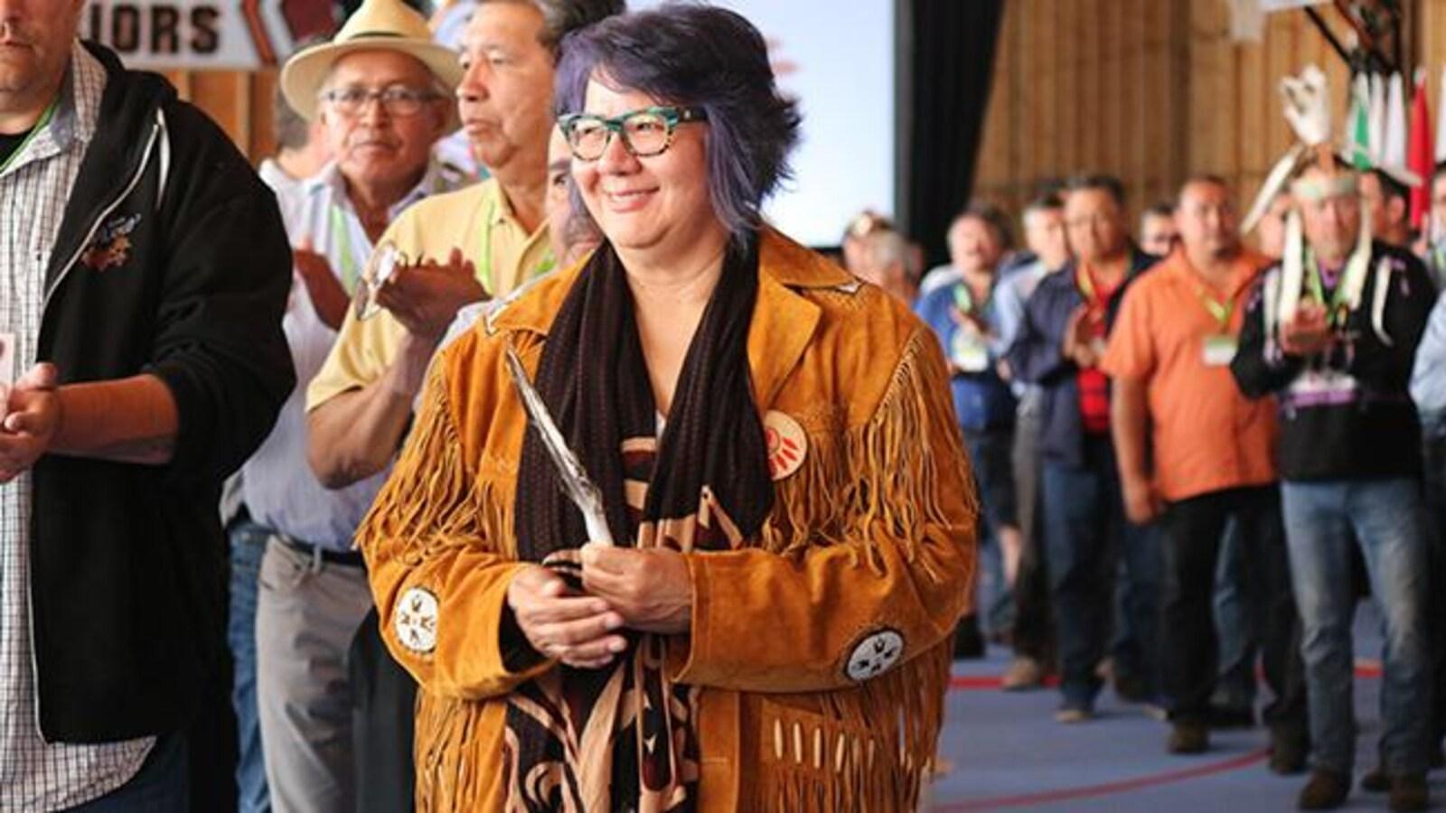 Une femme autochtone debout devant les personnes qui l'ont élue.