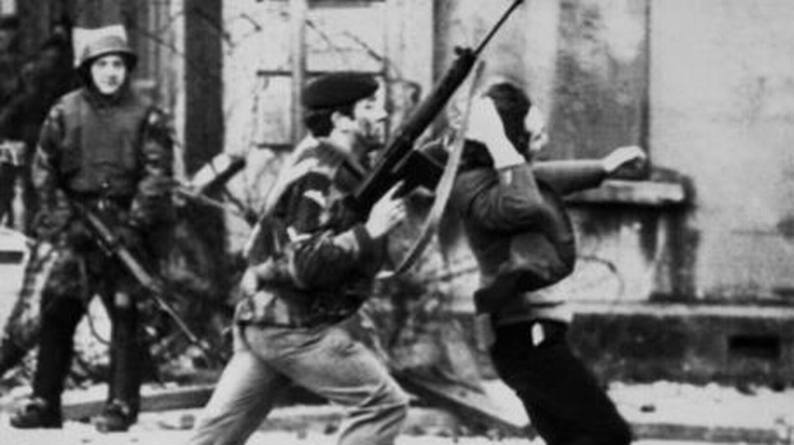 Un soldat empoigne un manifestant par les cheveux et le pousse vers l'avant.