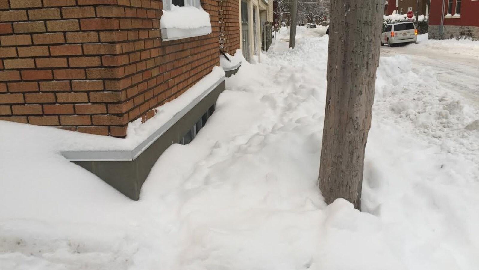 Beaucoup de neige sur les trottoirs de la rue Fraser. Difficile pour un piéton d'y circuler.
