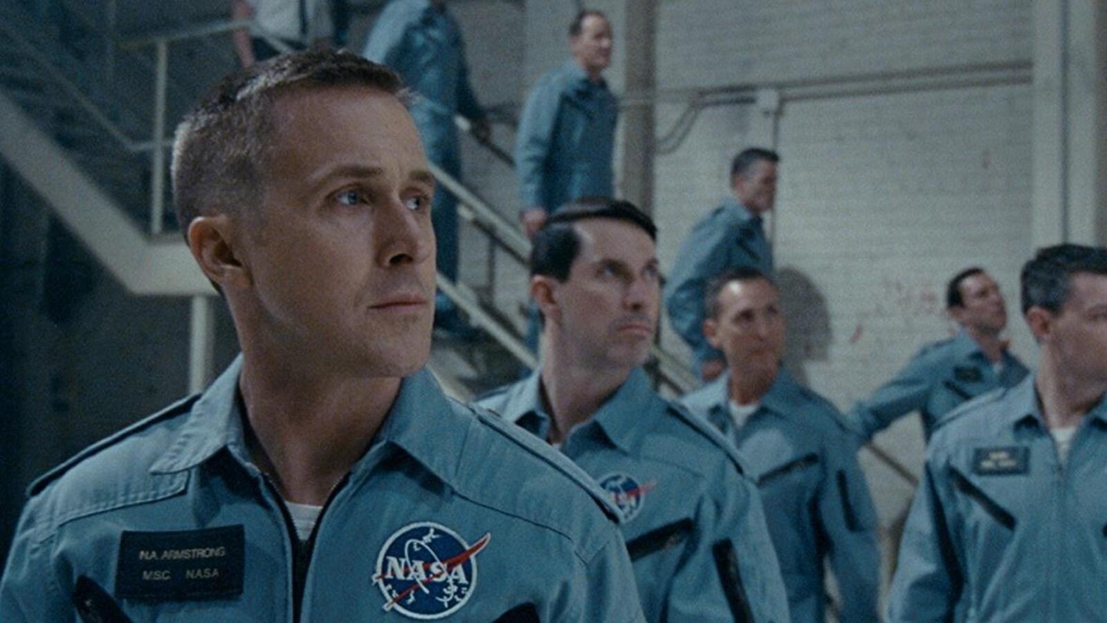 Ryan Gosling, en uniforme de la NASA, regarde vers la droite, tout comme d'autres astronautes derrière lui.