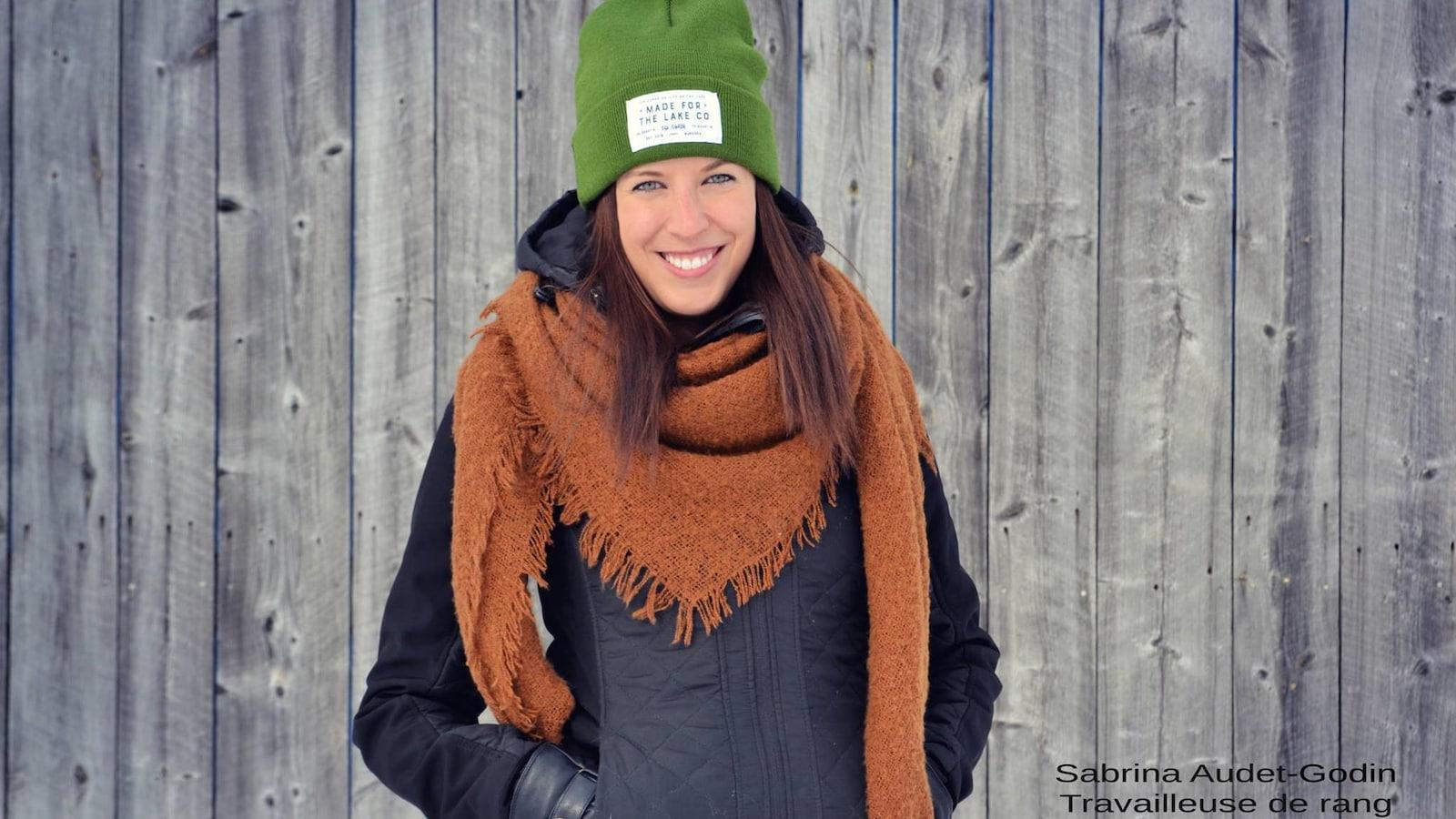 Une femme portant des vêtements d'hiver sourit à la caméra devant un mur de grange.