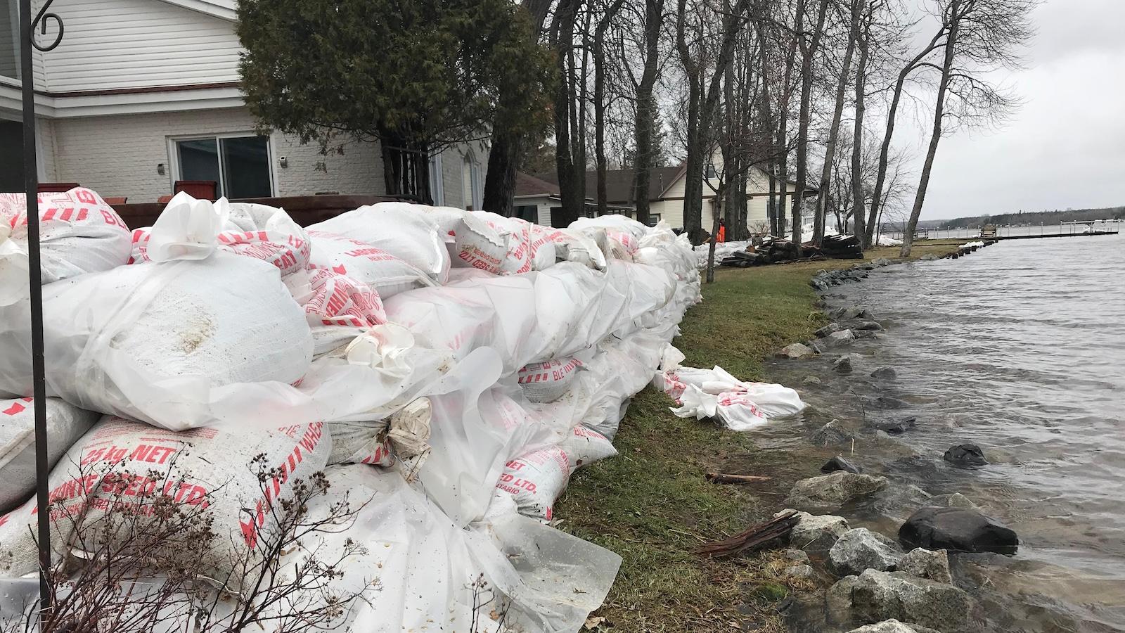 Des sacs de sable sont empilés aux abords d'un lac près de résidences.