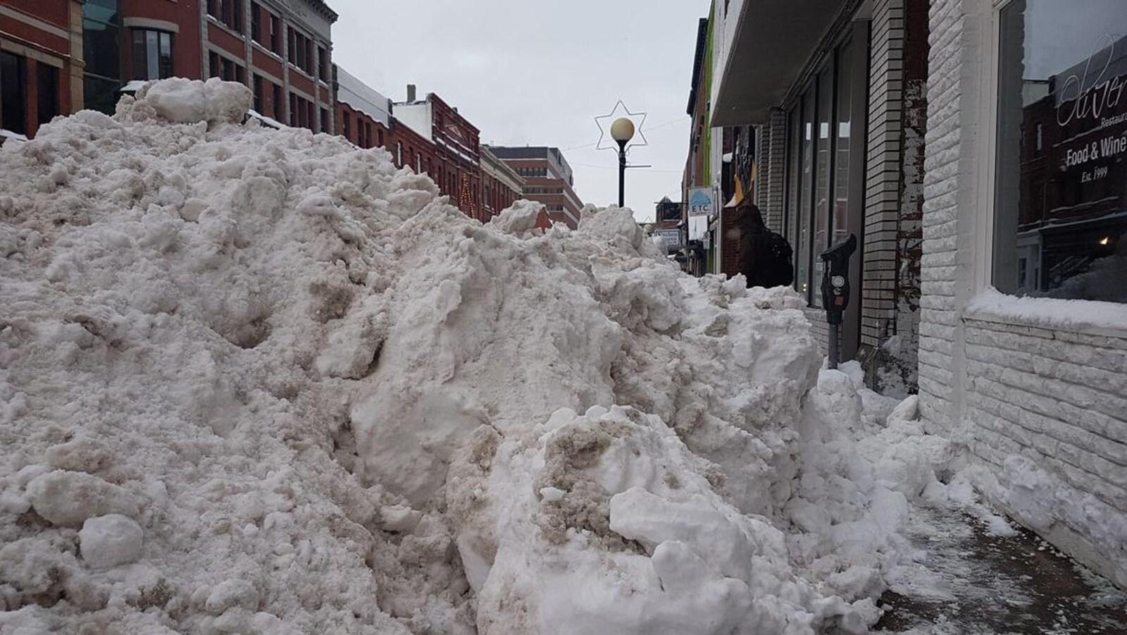 Un énorme monticule de neige bloque le trottoir devant le restaurant