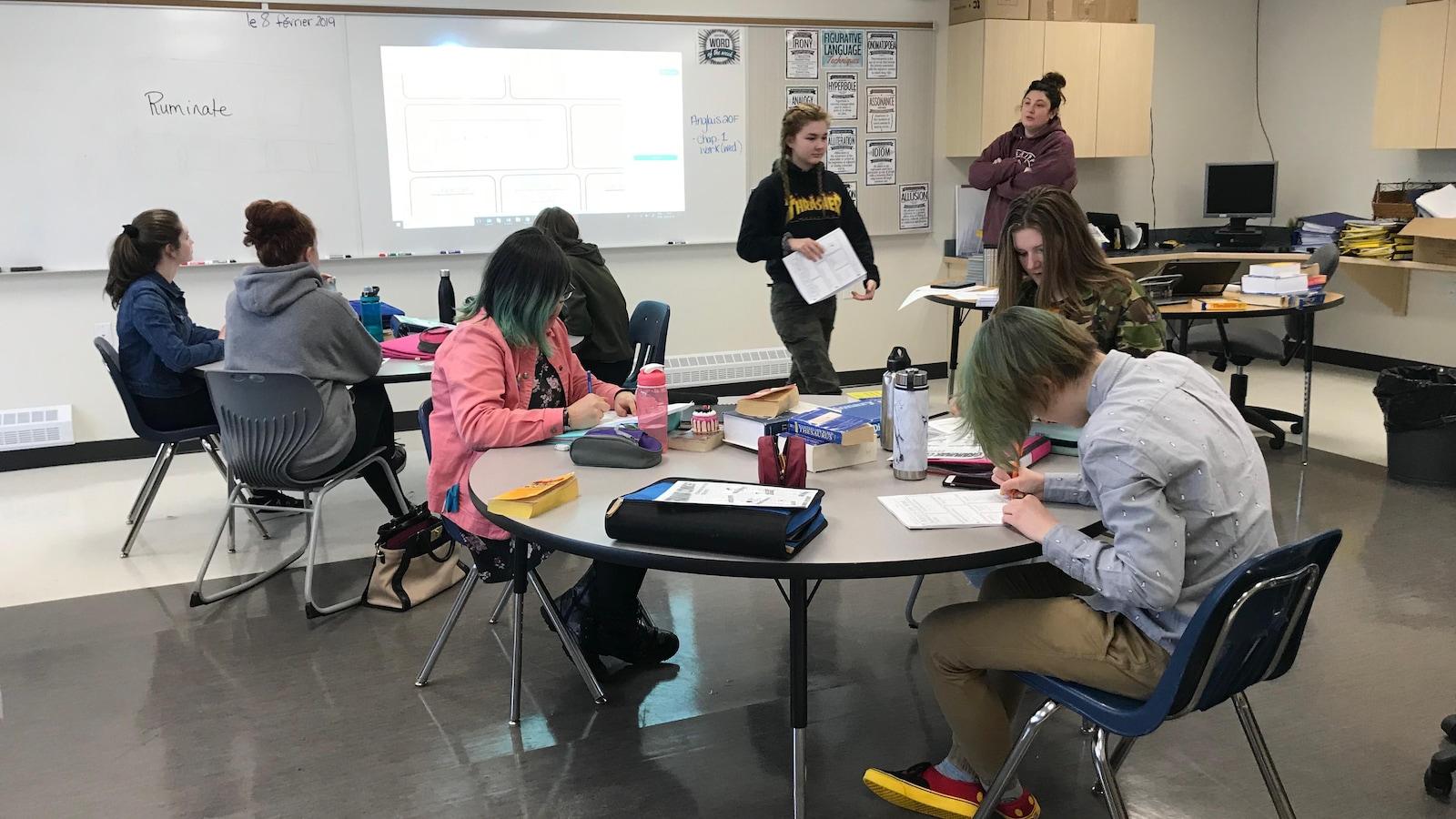 Des adolescents assis à des tables rondes dans une salle de classe