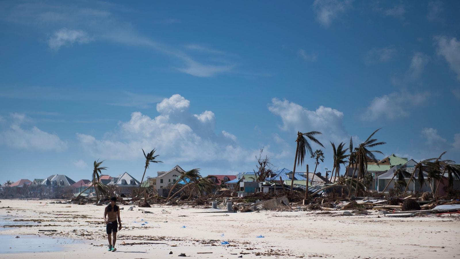 Un homme marche sur la plage lors d'une journée ensoleillée. Autour de lui, les palmiers sont presque déracinés et les habitations sont très endommagées.