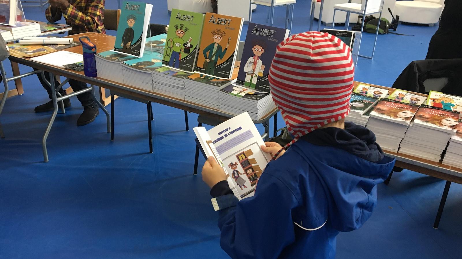 Un jeune garçon lit un livre.