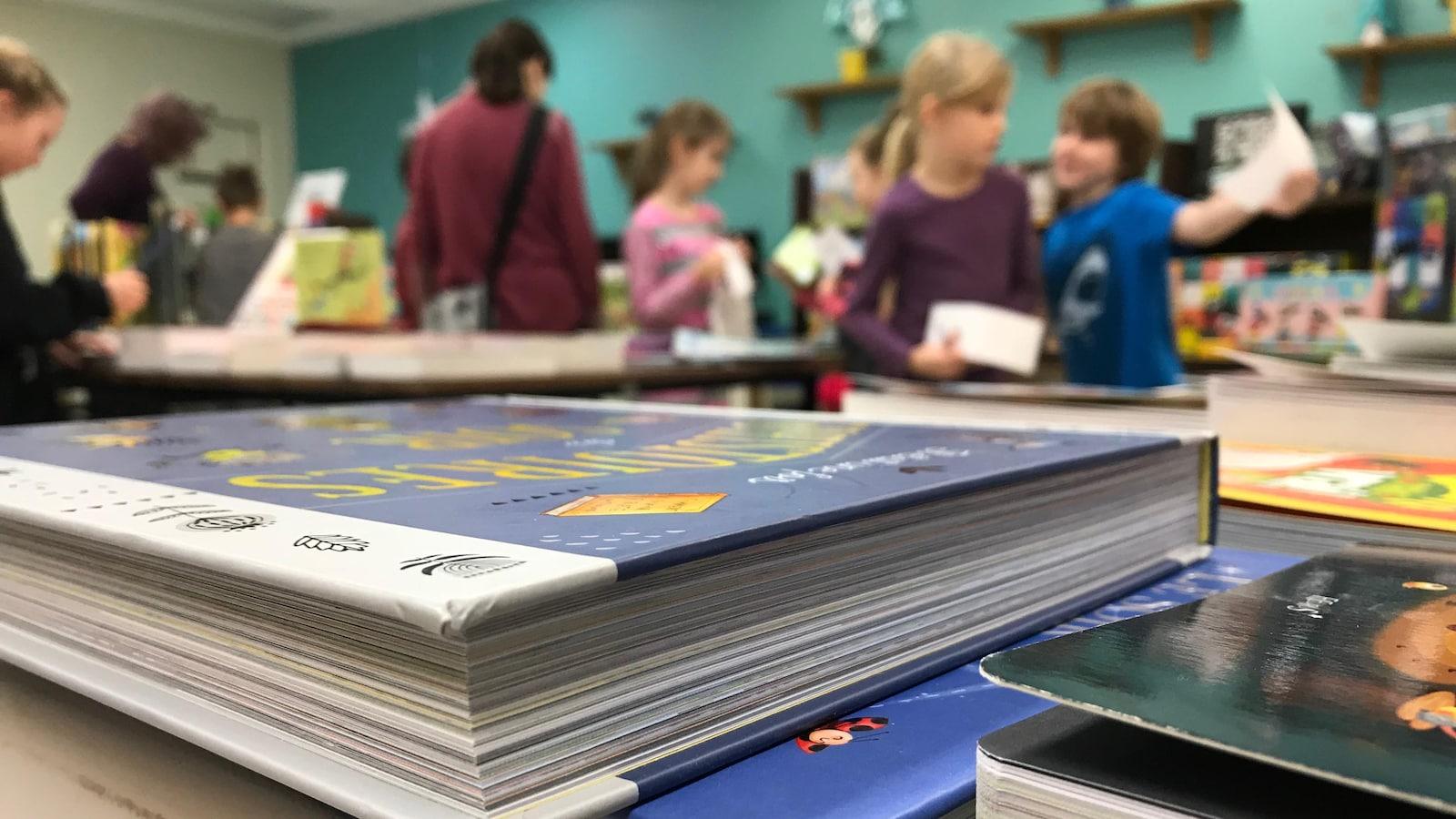 Des élèves magasinent lors d'un salon du livre dans une école.