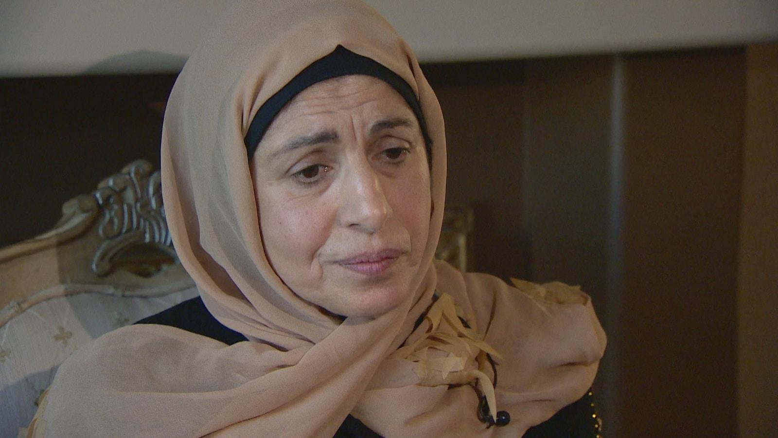 Salwa Atwi porte un hidjab brun. Elle a les yeux baissés et une expression triste.