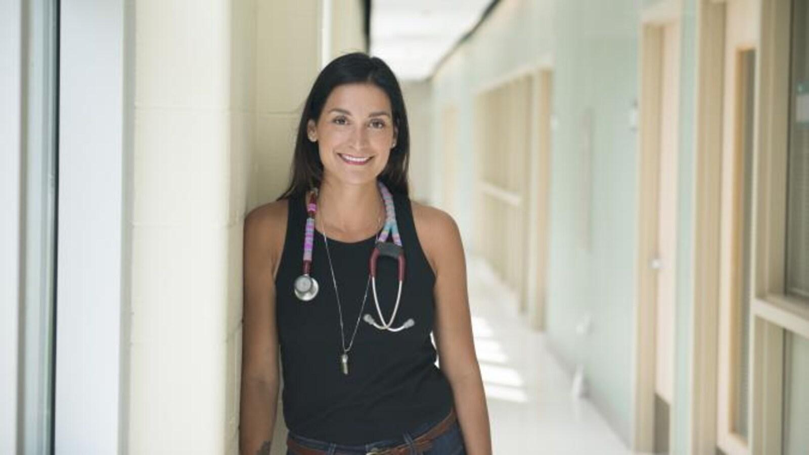 Portrait d'une femme dans un corridot. Elle porte un stéthoscope autour du cou.