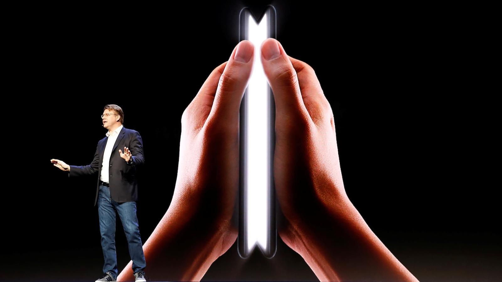 Un homme en veston sur une scène en train de parler avec un écran géant affichant un téléphone pliable derrière lui.