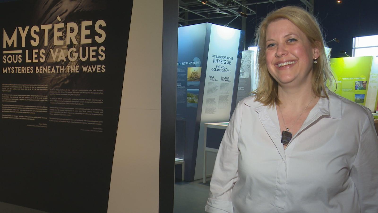 La directrice sourit devant une salle d'exposition du musée.