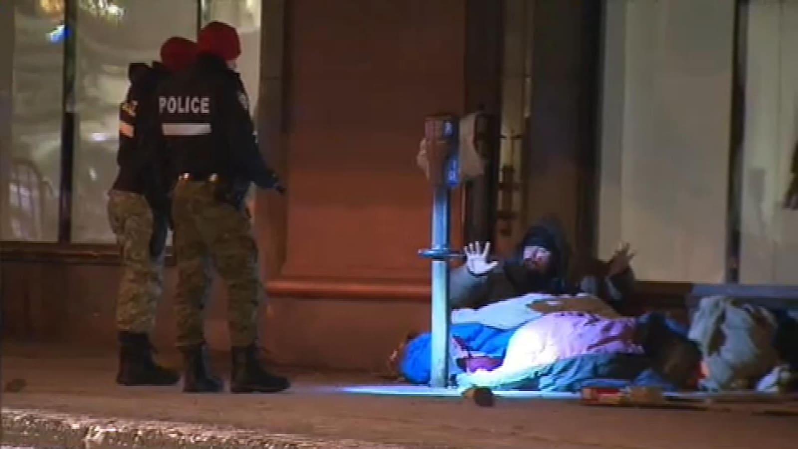 Deux policiers parlent avec un sans-abri qui dort devant un magasin du centre-ville de Montréal