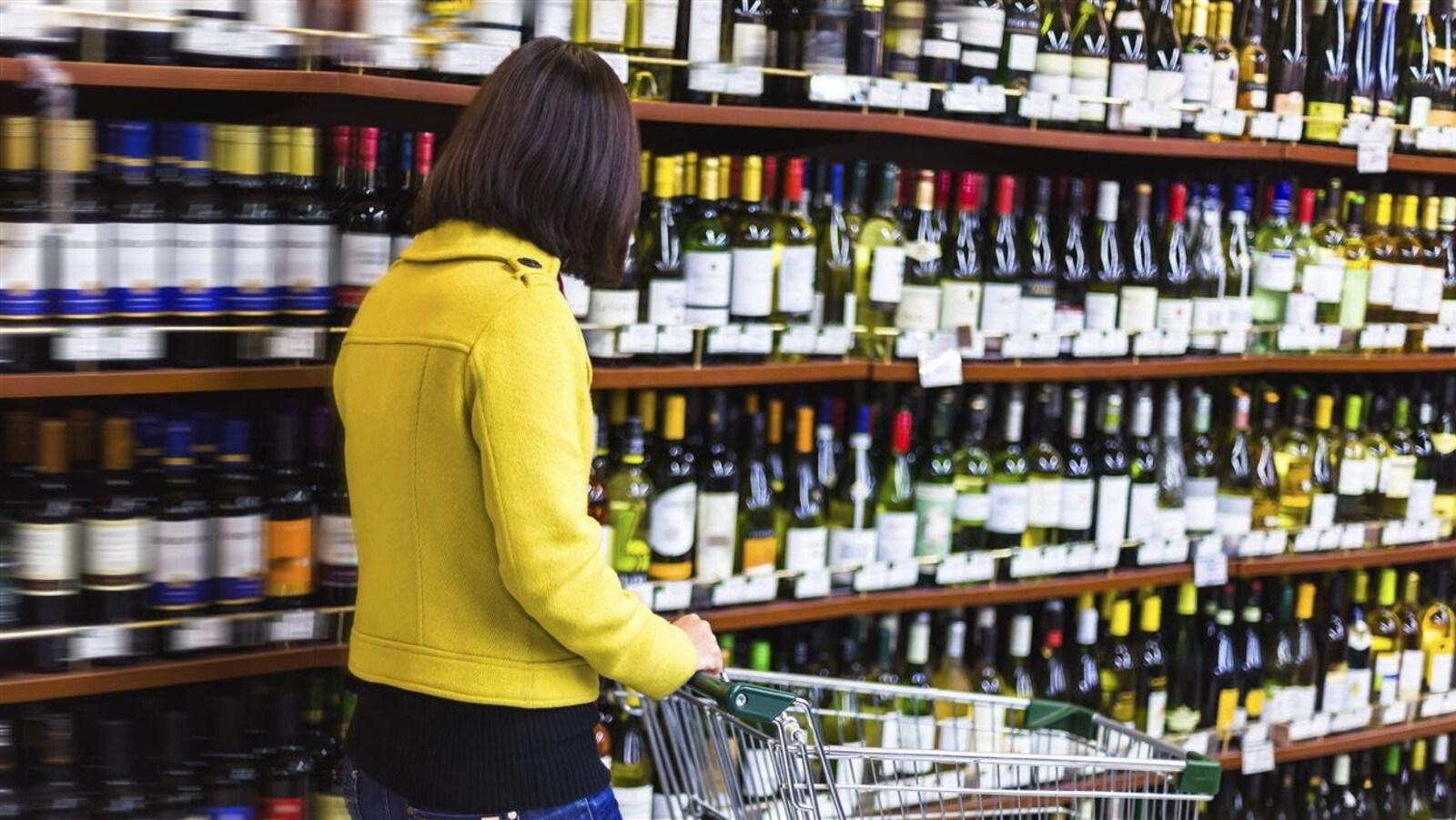 Une femme avec un panier dans une allée d'une succursale de la Société des alcools du Québec.