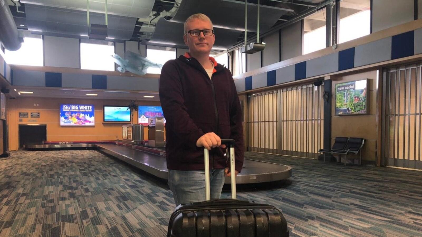 Un homme debout avec sa valise dans un aéroport.