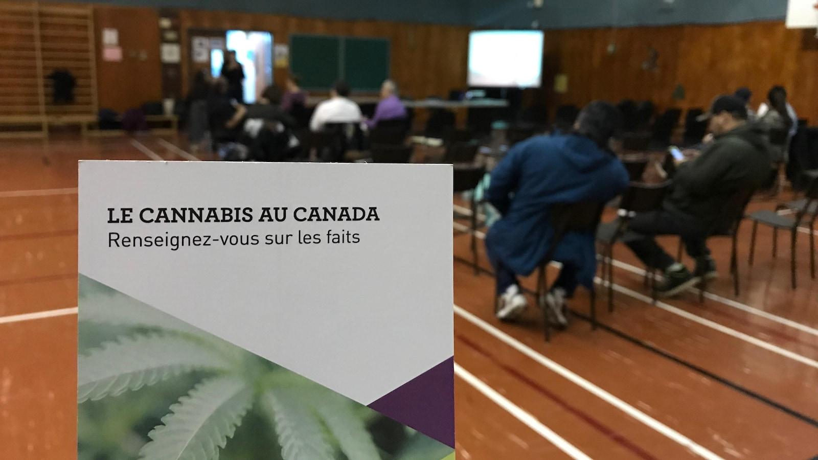 Un dépliant intitulé «Le cannabis au Canada - renseignez-vous sur les faits» est en premier plan lors d'une séance d'Information dans un gymnase.