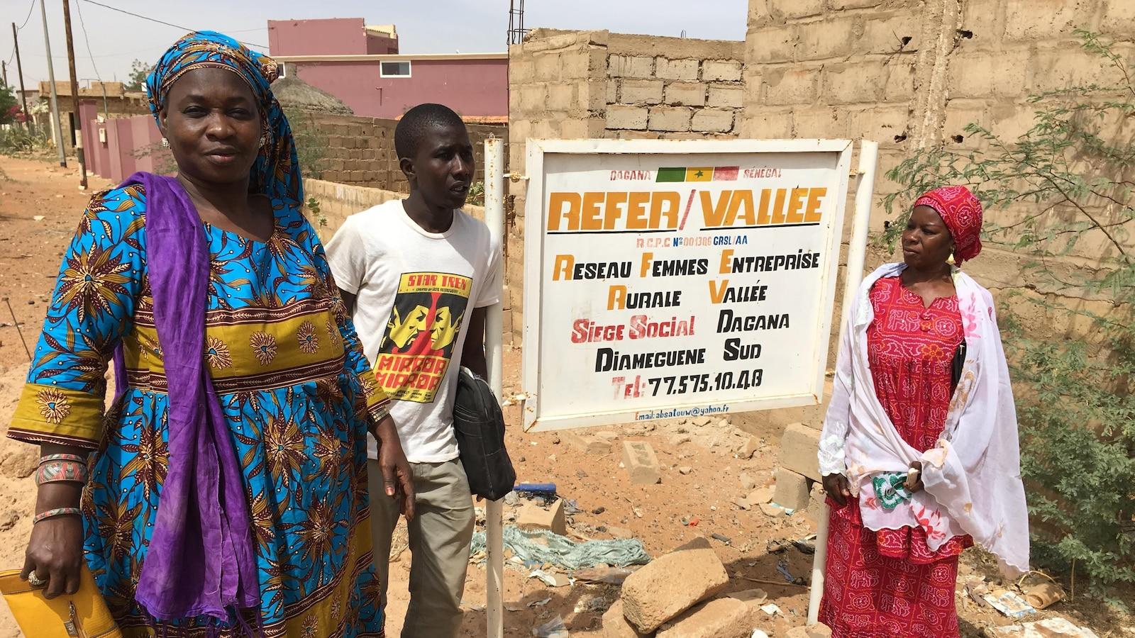 Lors d'une journée ensoleillée, deux femmes et un homme posent devant une pancarte sur laquelle on peut lire « Réseau femmes entreprise rurale vallée ».