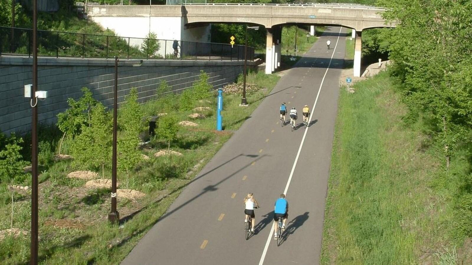 Un large sentier pour vélo entouré de végétations, sur lequel circulent quelques personnes.