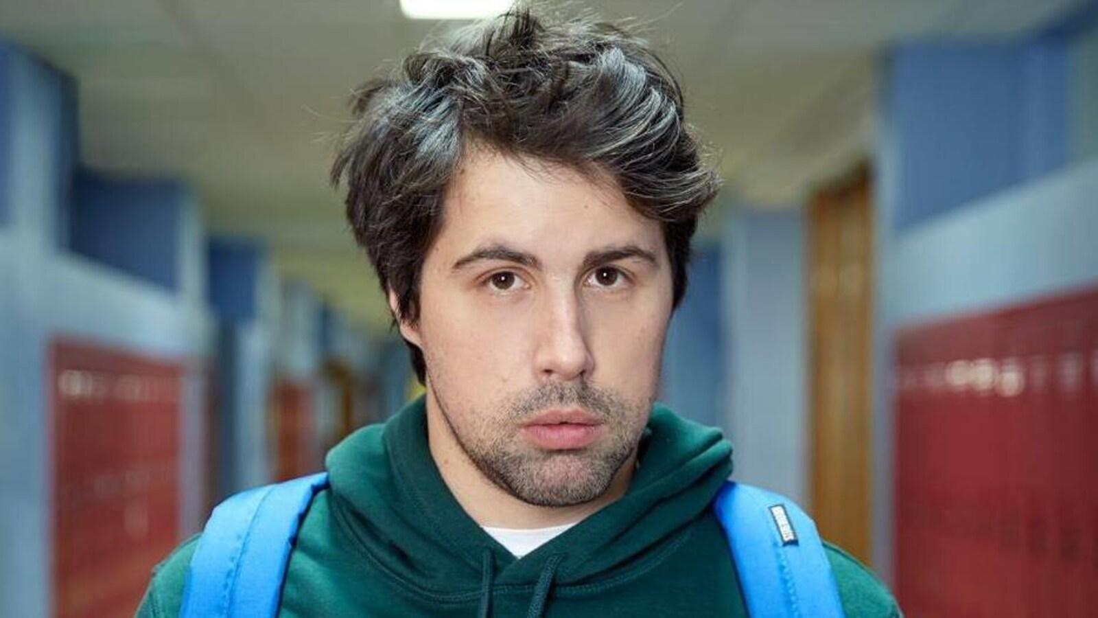 Philippe-Audrey-Larrue-St-Jacques est dans un couloir d'école, et porte un sac à dos.