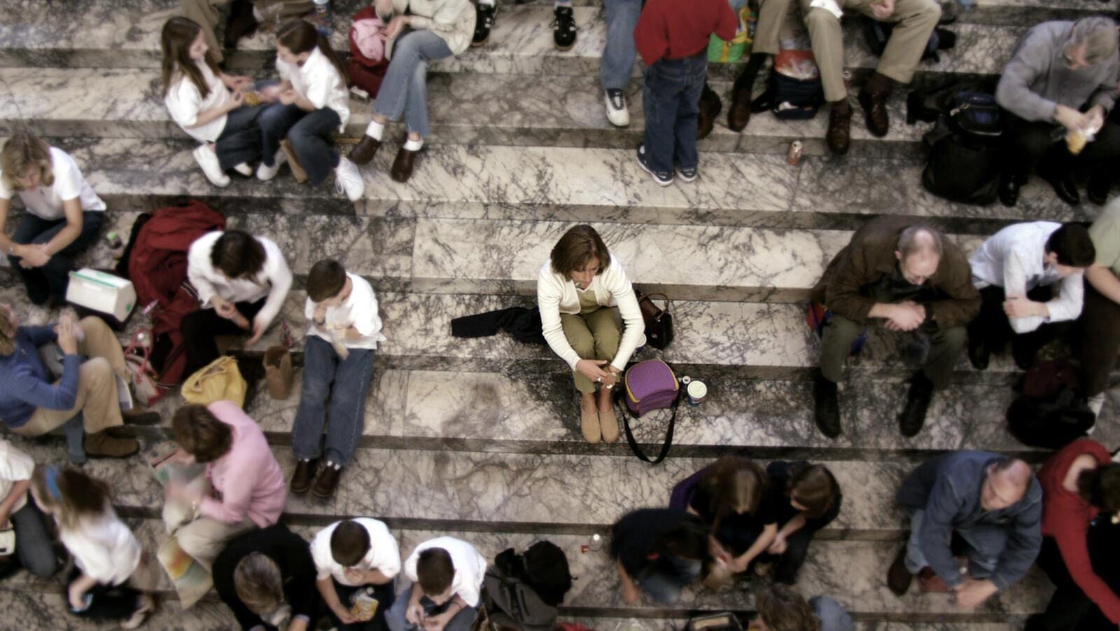 Une femme est assise sur les marches d'un escalier. Elle est entourée d'une foule.