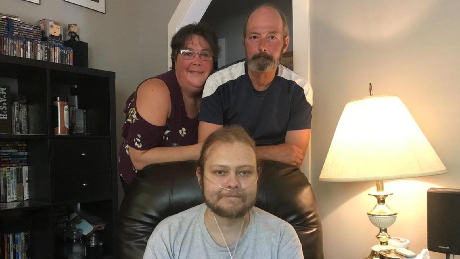 Un jeune homme malade assis dans son salon et entouré par ses parents.