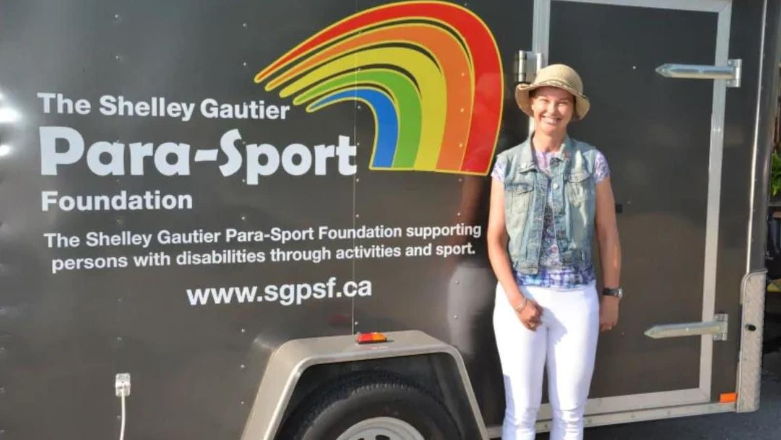 La paracycliste Shelley Gautier devant le logo de sa fondation.