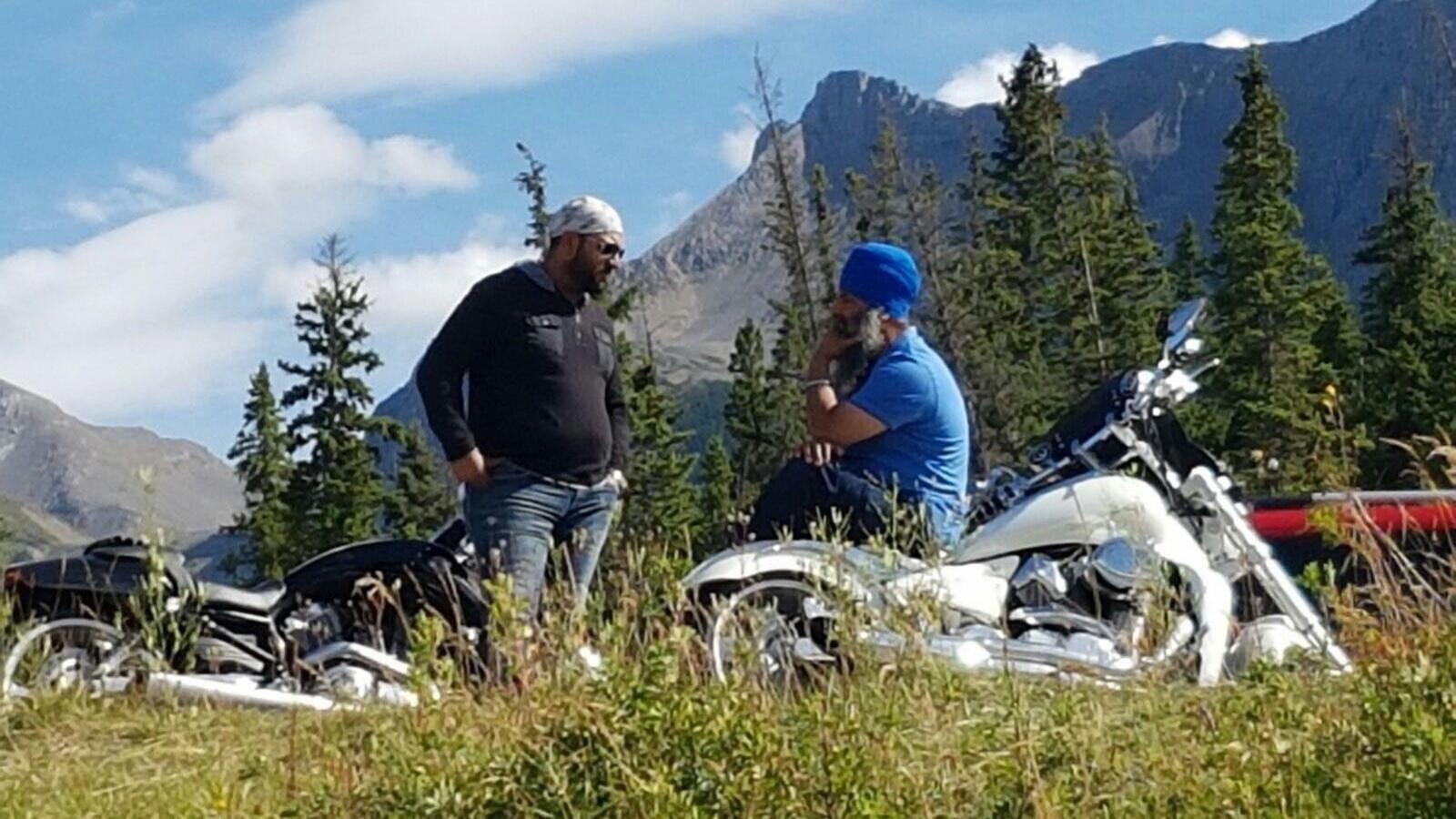 Un homme portant le turban sikh est assis sur une moto, tandis qu'un autre portant un foulard se tient debout, près d'une deuxième moto.