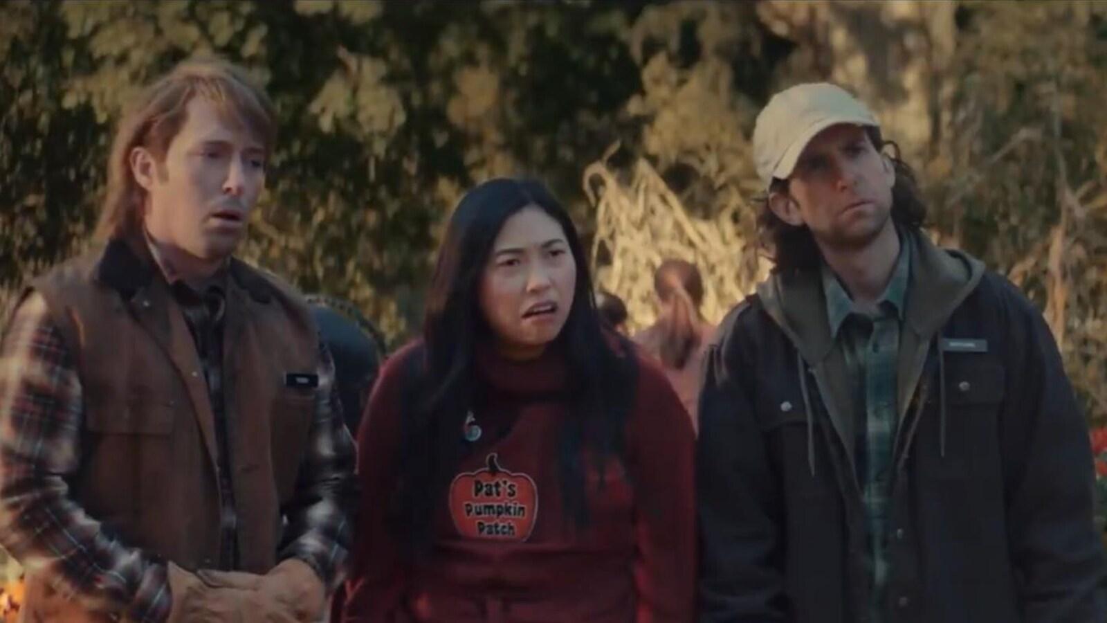 Trois personnes se tiennent debout dans un champ de citrouilles et ont la bouche ouverte, l'air étonné.
