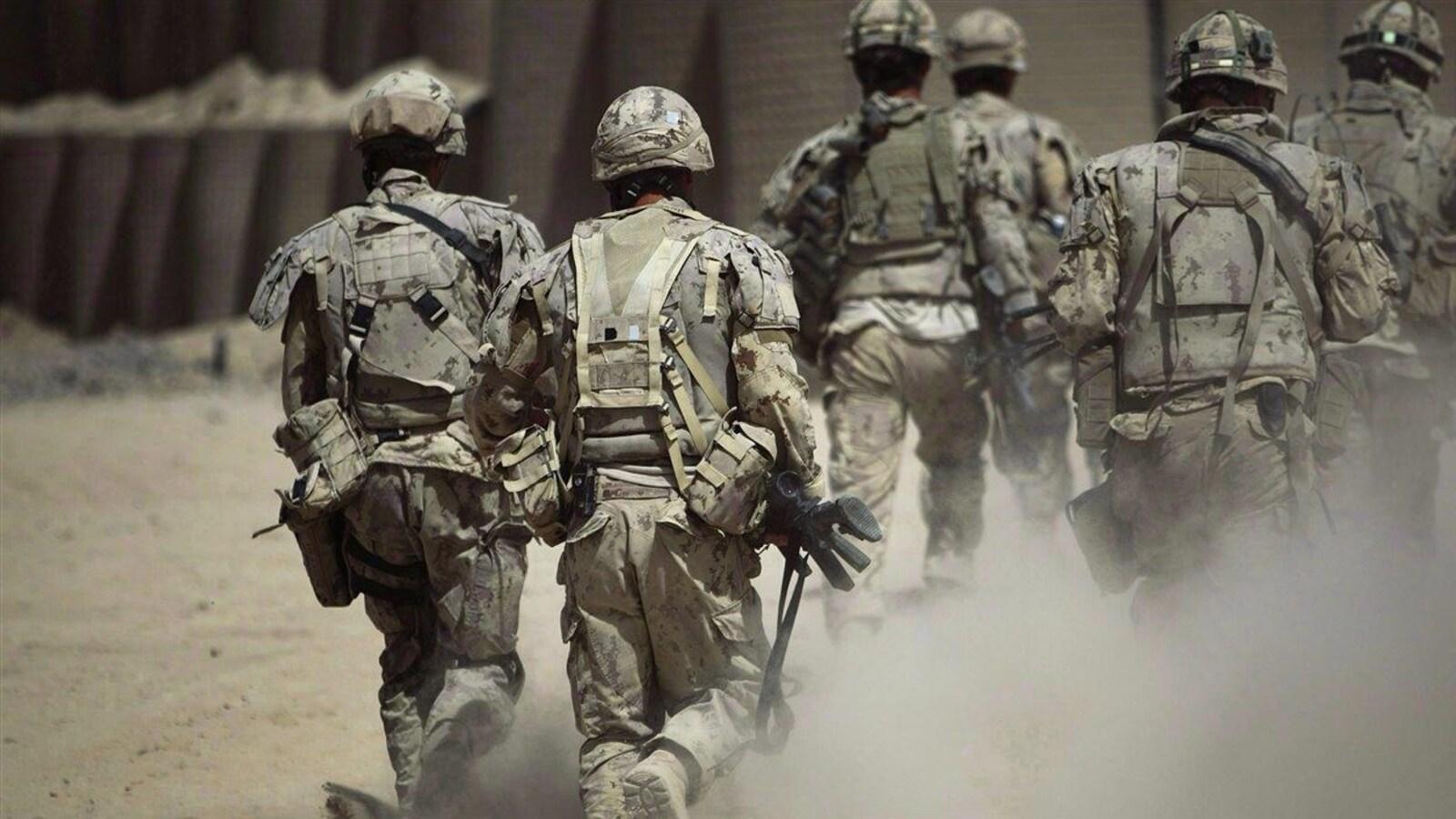 Des soldats en habit de camouflage marchent dans la poussière. Ils sont photographiés de dos.