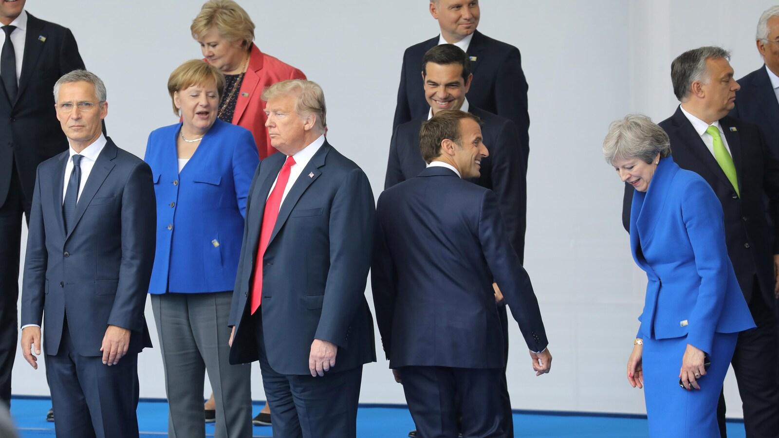 Donald Trump se tient très droit alors qu'Emmanuel Macron lui tourne le dos.