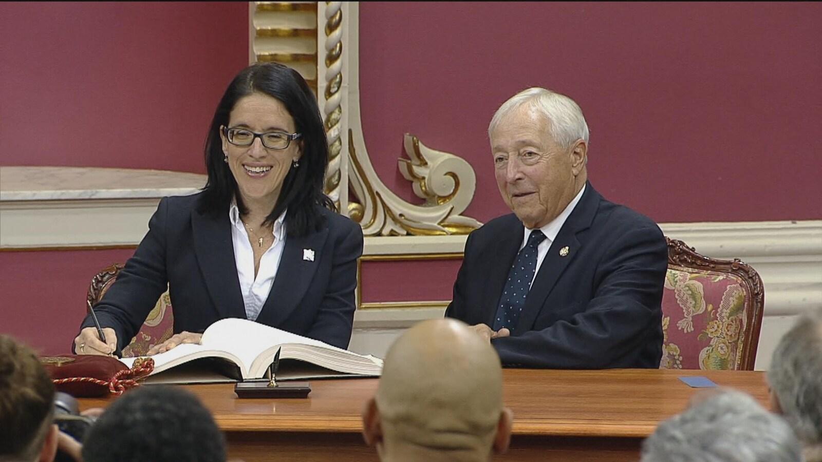 Sonia Lebel qui signe aux côtés du Lieutenant-gouverneur.