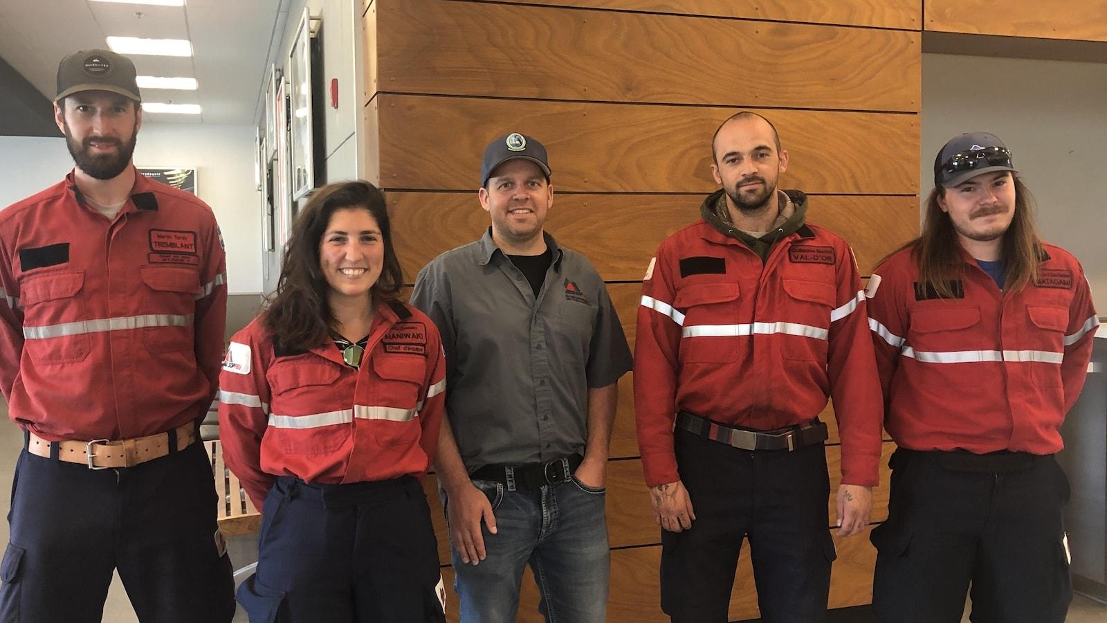 Cinq employés de la SOPFEU posent côte à côte à l'aéroport de Val-d'Or.