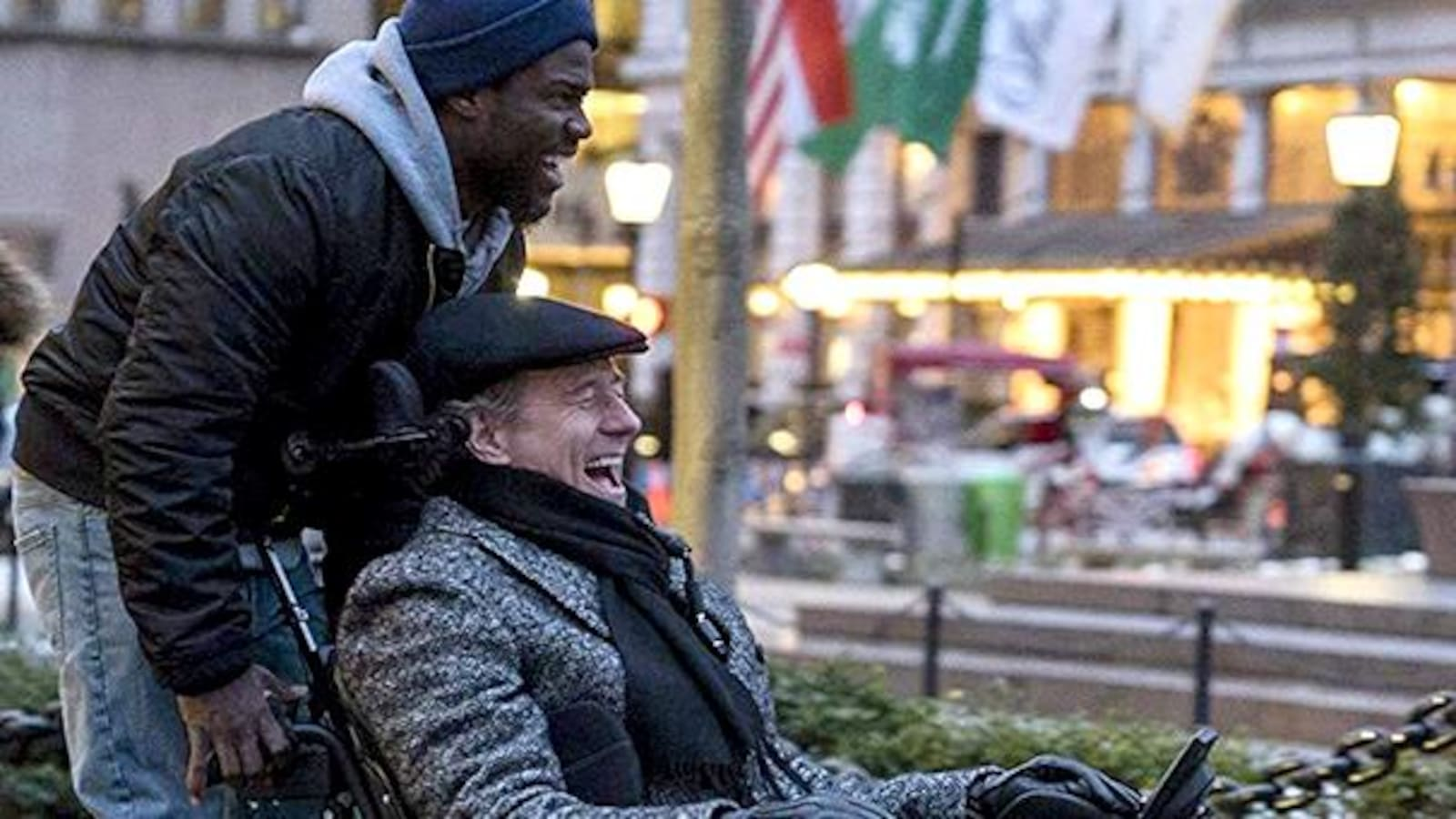 Un homme pousse un autre homme dans un fauteuil roulant et ils rient.