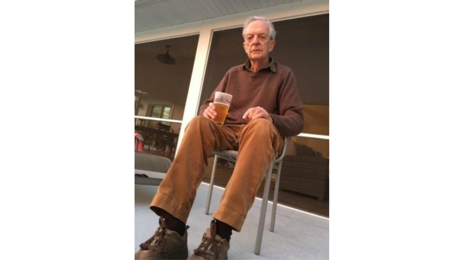 Photographie d'un homme âgé assis sur une chaise avec un verre dans la main droite posé sur sa cuisse droite.