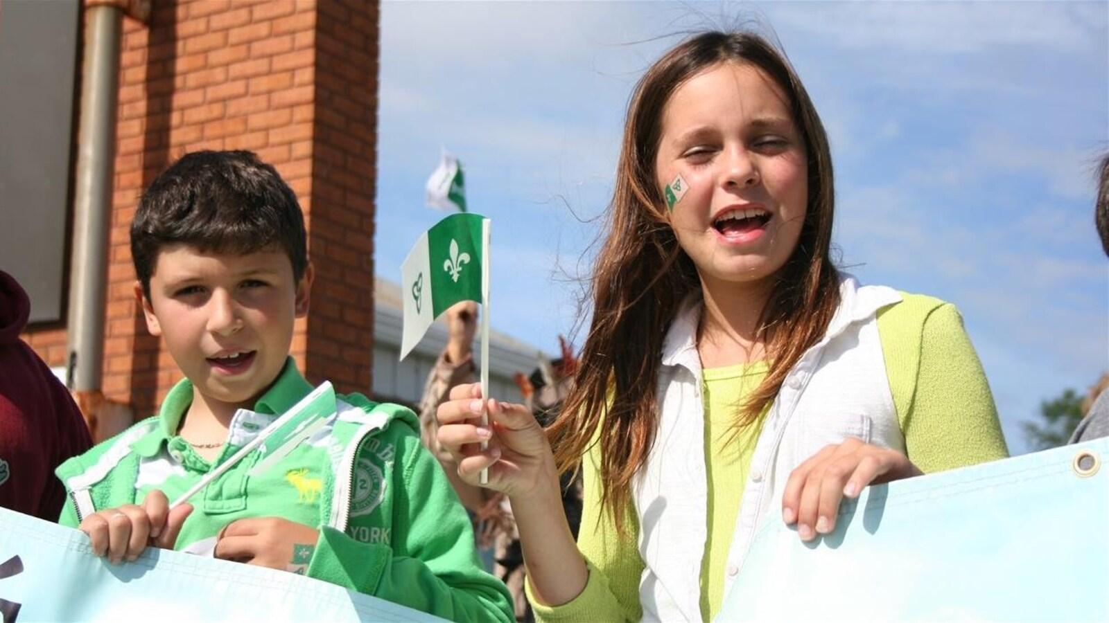 Deux enfants brandissent le drapeau franco-ontarien à la Saint-Jean-Baptiste dans le Grand Sudbury.