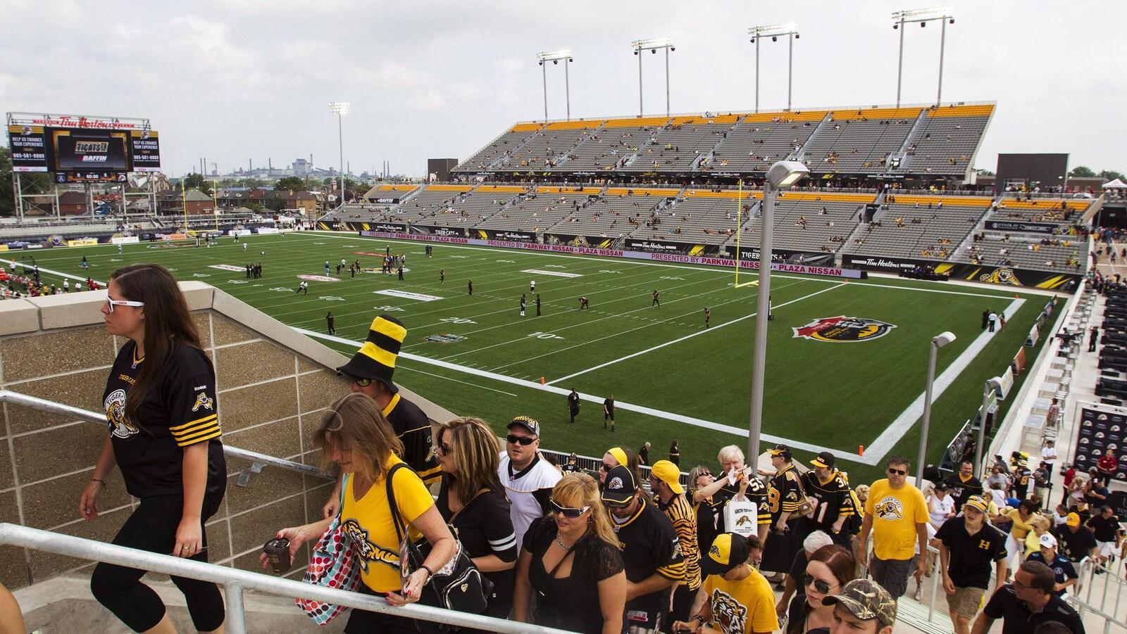 Photo de spectateurs qui montent les marches dans les gradins.