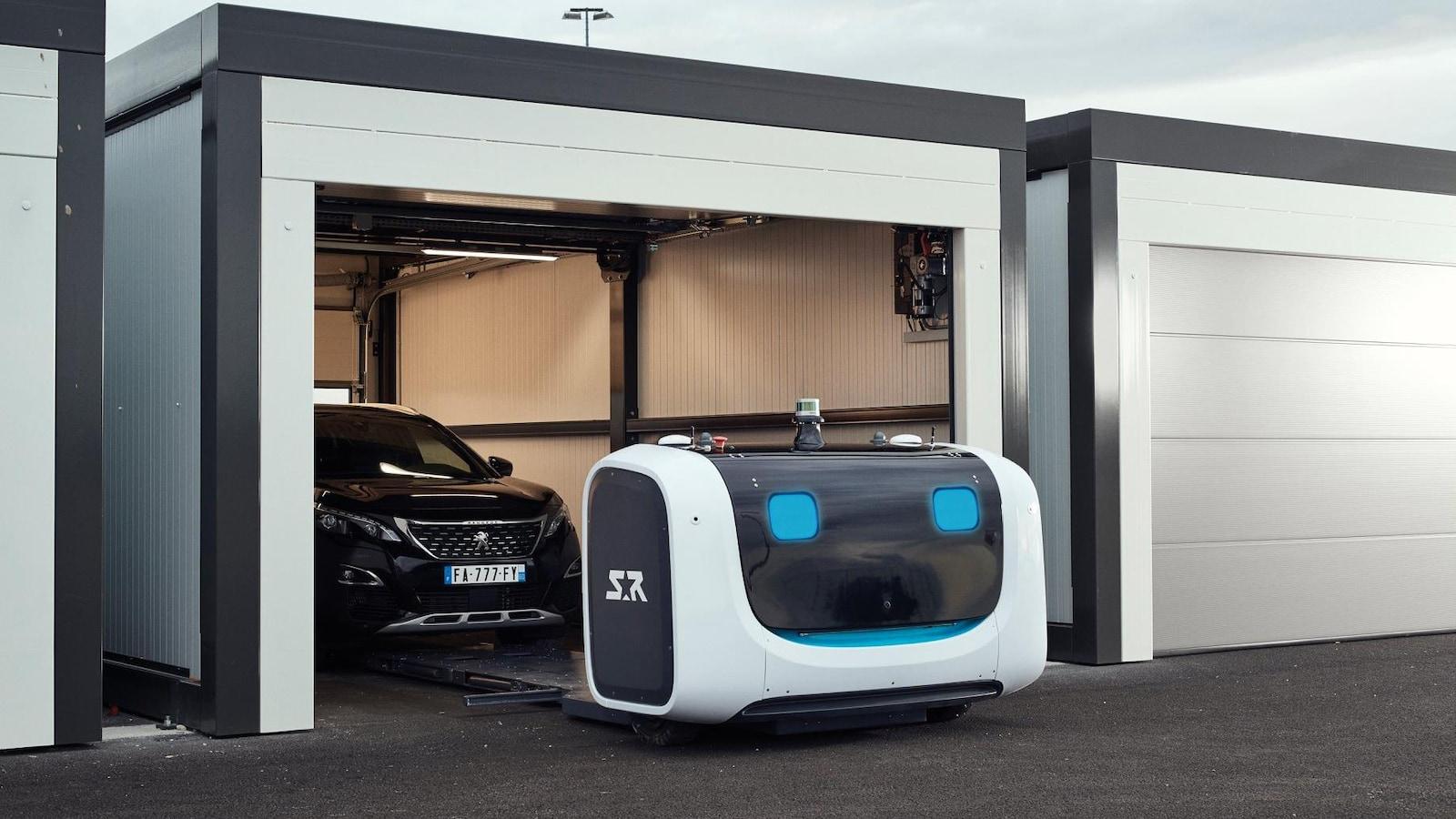Une photo montrant le robot Stan en train de déposer une voiture dans un garage. Le robot est composé d'une mince plate-forme métallique et d'une grande boîte à l'avant contenant l'équipement électronique.