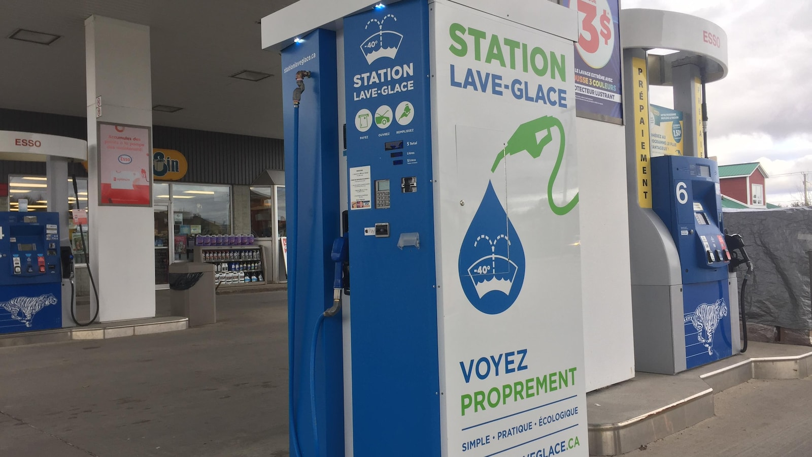 À côté d'une pompe à essence, une pompe à lave-glace qui utilise sensiblement le même procédé pour distribuer du lave-glace aux clients.