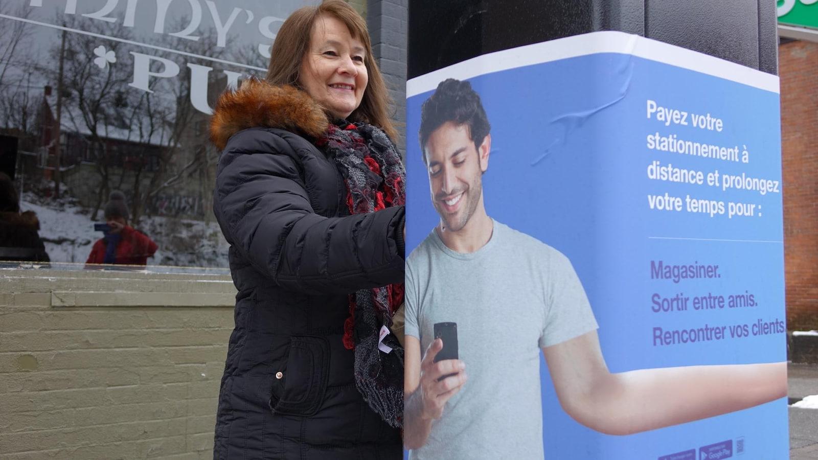 La conseillère municipale Nicole A. Gagnon paie son stationnement dans une borne ou est affichée une publicité pour une nouvelle application
