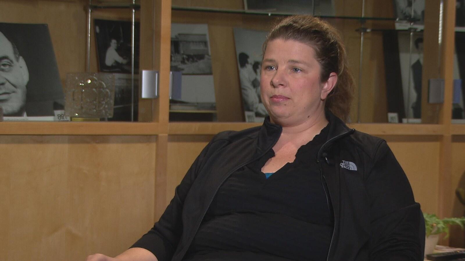 Elle est assise dans les studios de Radio-Canada pour une entrevue. Elle a les cheveux attachés et porte des vêtements noirs.