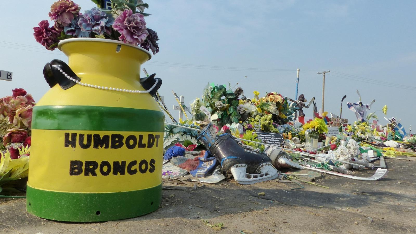 Un pot de fleurs de couleurs verte et jaune sur lequel il est inscrit Humbolt Broncos, accompagner de plusieurs objets significatifs, comme des patins à glace.
