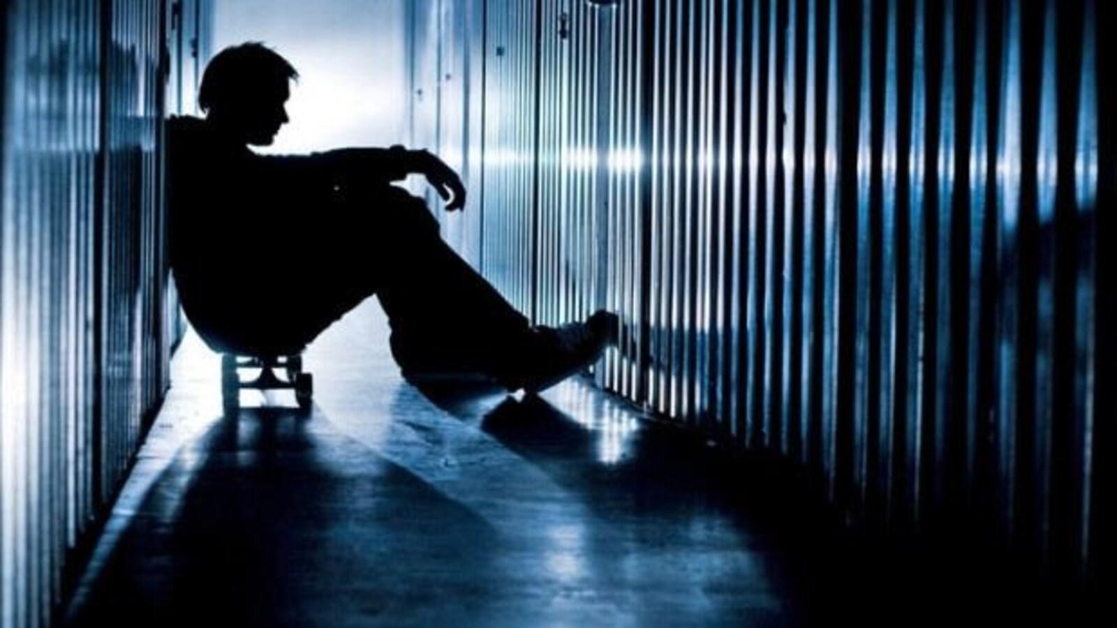 Un jeune assis dans la pénombre, sur une planche à roulette, dans un couloir sombre.