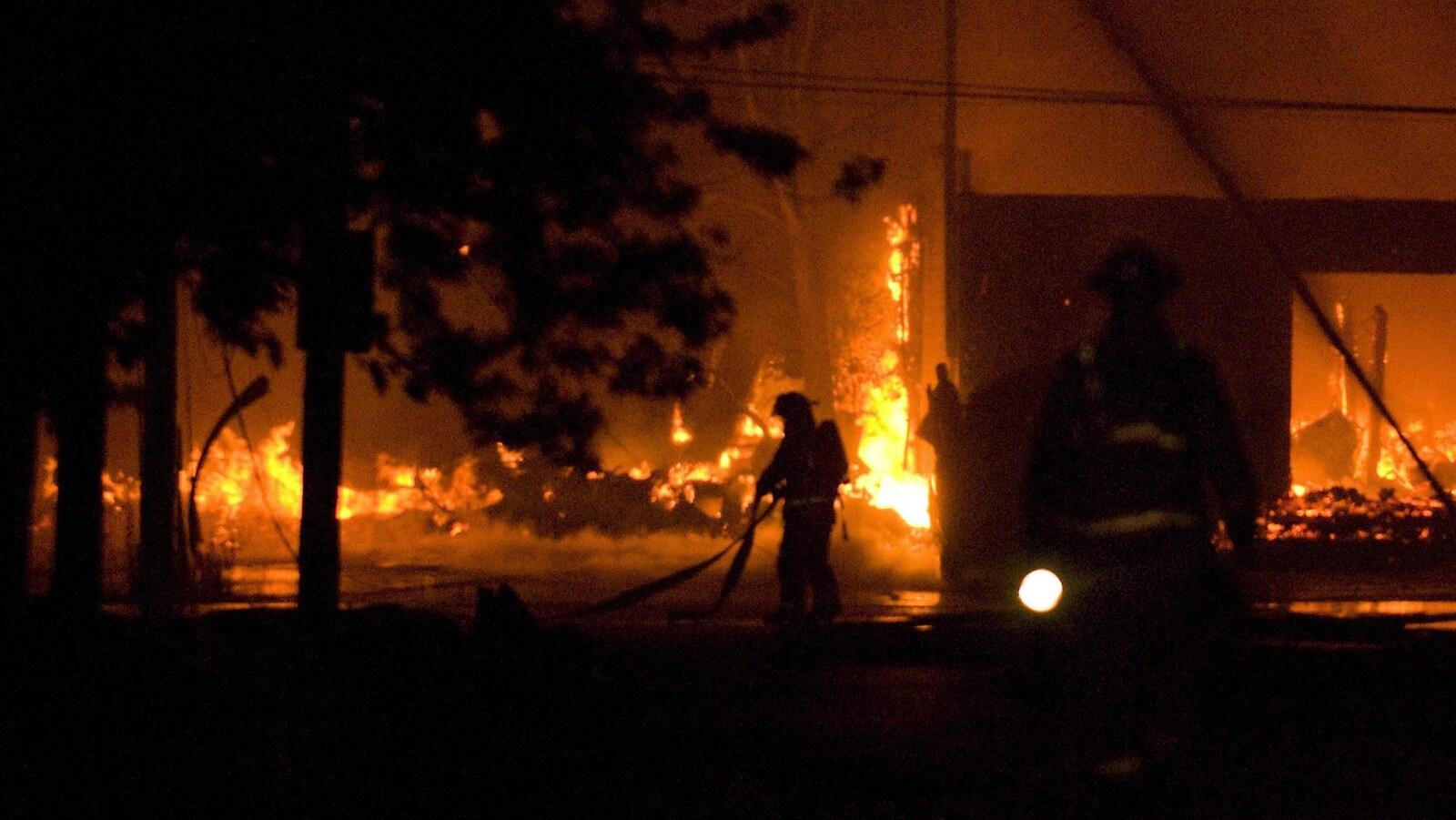 Des pompiers qui tentent d'éteindre les flammes.