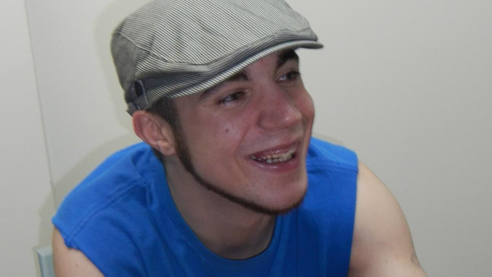Vue sur un jeune homme qui sourit avec un chandail et une casquette.
