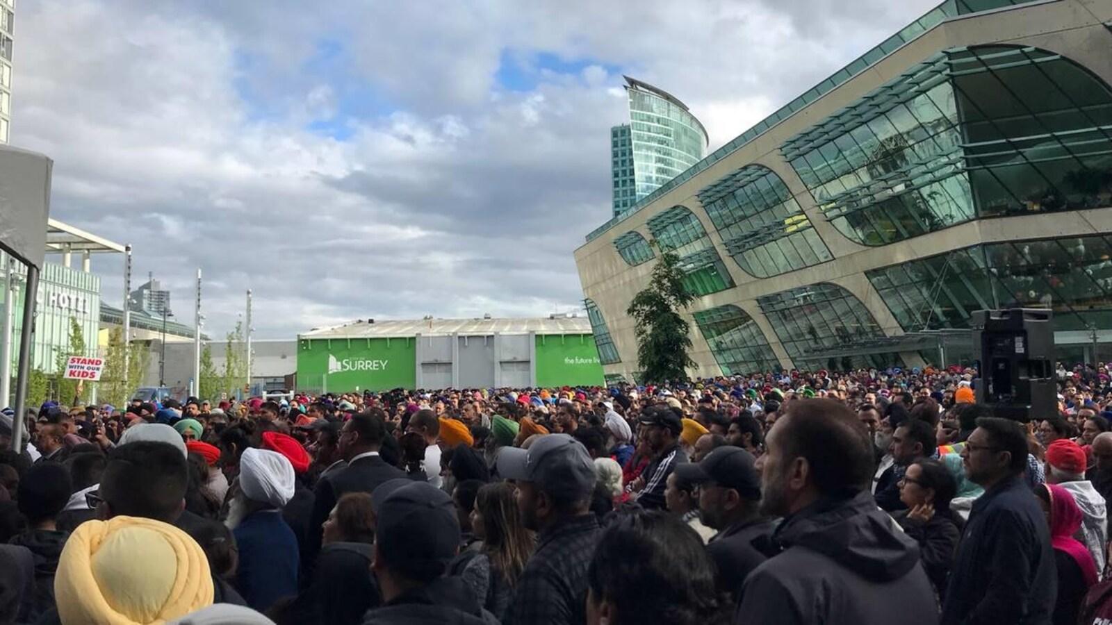 Des milliers de personnes sont entassées sur une grande place devant un immeuble de quelques étages.