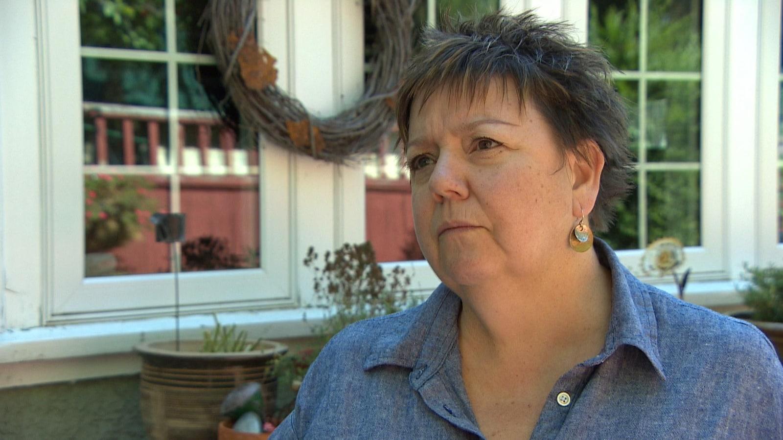 Une femme aux cheveux courts, en entrevue devant la façade d'une maison.