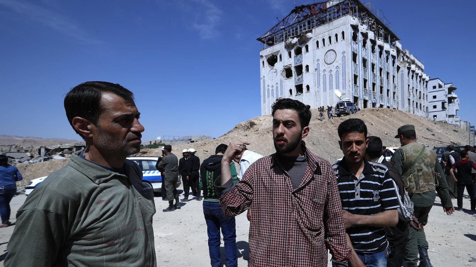 Plusieurs hommes sont rassemblés devant un hôpital de Douma, visiblement endommagé par des obus. Des militaires syriens sont situés tout près.