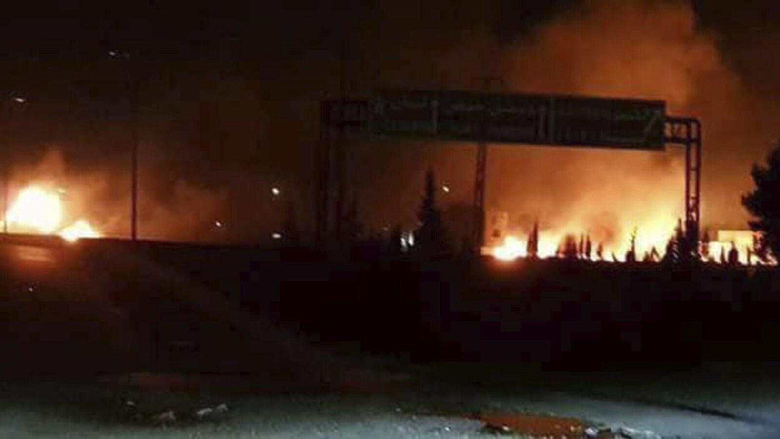 Cette photo rendue publique par l'agence de presse officielle syrienne SANA, montre des flammes se levant après une attaque dans une zone connue pour avoir de nombreuses bases militaires de l'armée syrienne, à Kisweh, au sud de Damas, en Syrie.