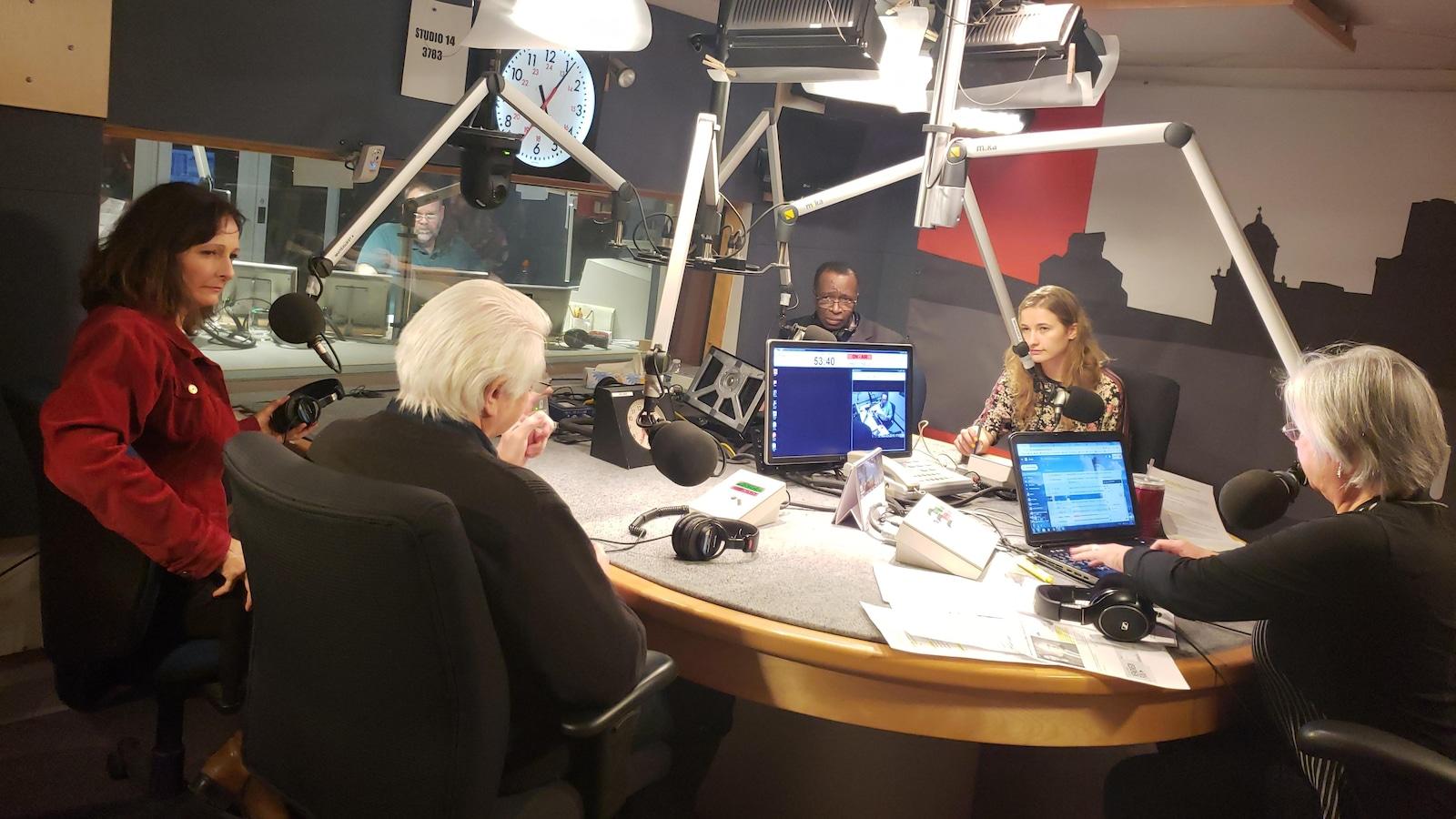 Plusieurs personnes autour d'une table et de micros dans un studio de Radio-Canada.