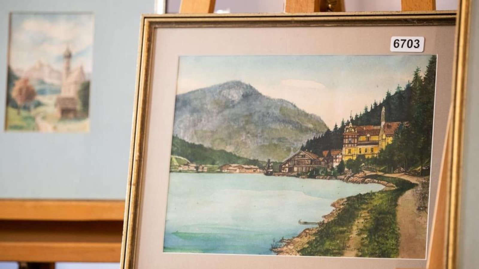 Tableau représentant un village allemand au bord de l'eau avec une montagne au fond.