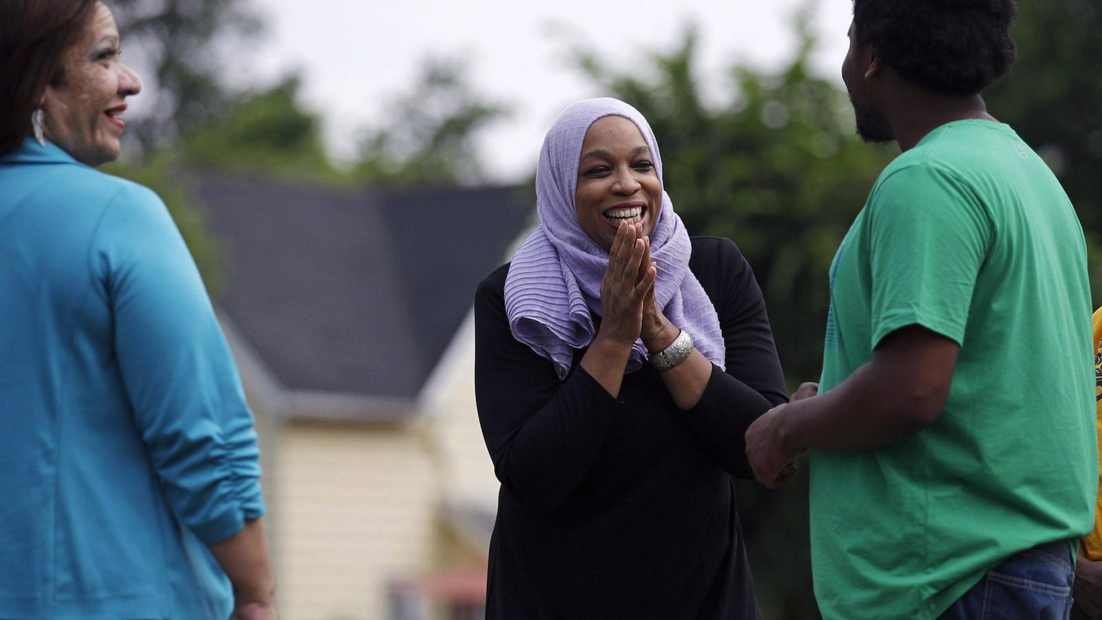 Tahirah Amatul-Wadud, entourée d'une femme et d'un homme.